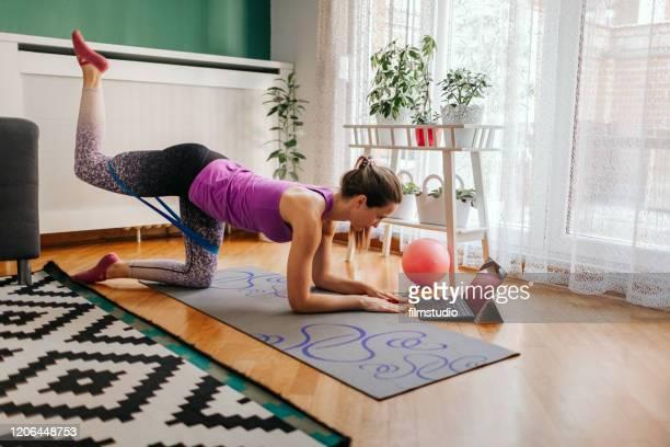 sportliche frau macht pilates-übung zu hause - turner syndrome stock-fotos und bilder