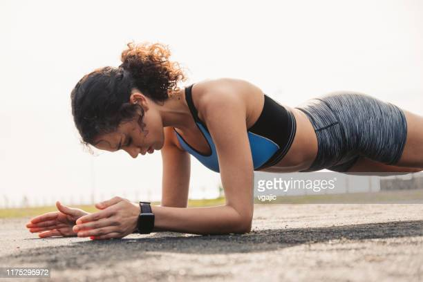 sporty woman doing plank exercise at park - plank position stock pictures, royalty-free photos & images