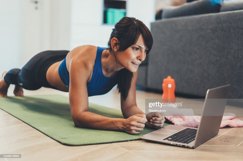 Sporty woman doing plank in front of her laptop : Foto de stock