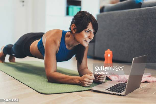 sporty woman doing plank in front of her laptop - exercising stock pictures, royalty-free photos & images
