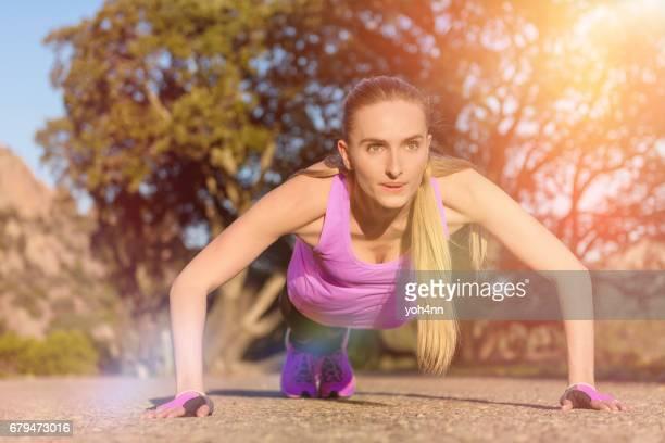 Sporty woman doing push-ups outside