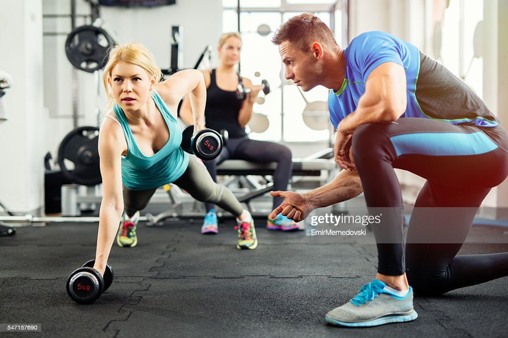 Sporty woman doing push-ups under supervision of  personal trainer. : Stock Photo