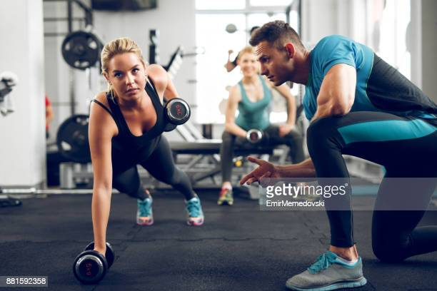 Sporty woman doing push-ups under supervision of personal trainer.