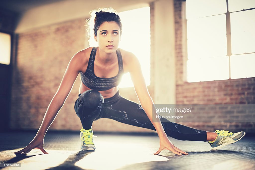 Sporty woman doing stretching exercise before workout in gym : Stock Photo
