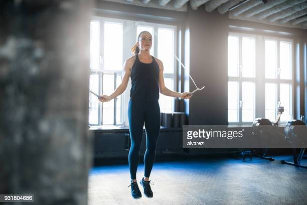 sporty woman doing workout with jump rope in gym - skipping along stock pictures, royalty-free photos & images