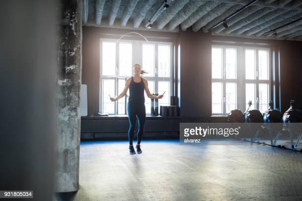 sportliche frau dabei training mit springseil im fitness-studio - skipping along stock-fotos und bilder