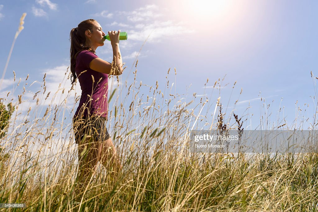 sporty woman drinking some water in nature : Stock Photo