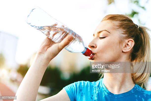 Sportliche Frau trinkt Wasser