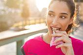 Sporty woman eating energy bar