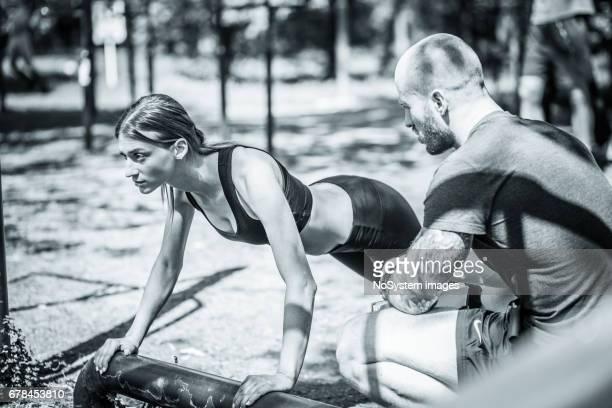Sportieve vrouw trainen met Fitnesstrainer buiten in het bos.