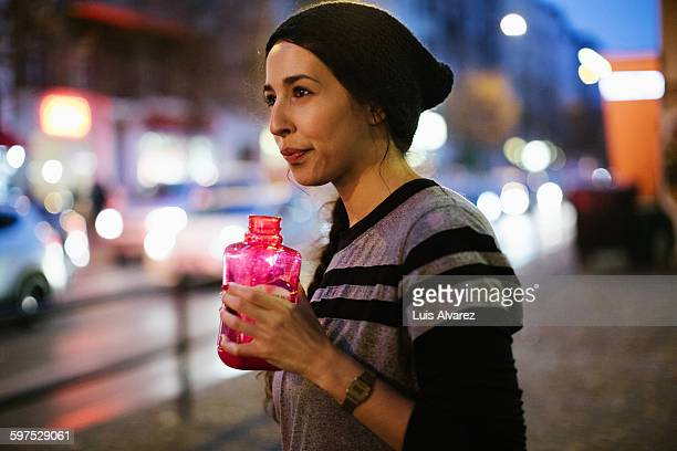Sporty woman holding water bottle on sidewalk