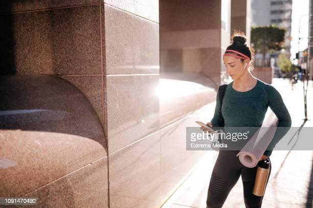 mulher desportiva ouvir música com os fones de ouvido sem fio, em área urbana - mobile - fotografias e filmes do acervo