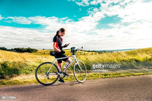 sporty woman on racing bicycle uses mobile phone while exercising on country road - bicycle stock pictures, royalty-free photos & images