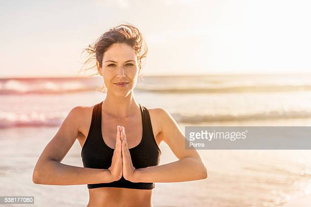 Sporty woman practicing yoga at beach