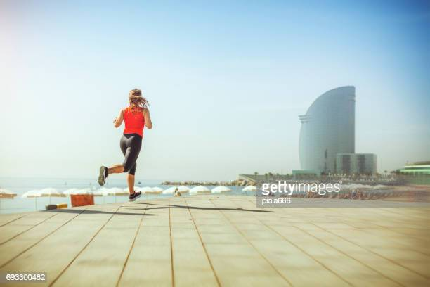 sporty woman running and training alone - la barceloneta stock pictures, royalty-free photos & images