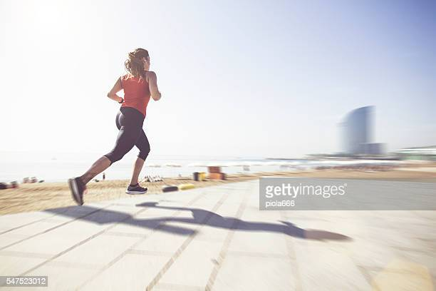 sporty woman running and training by the beach - la barceloneta stock-fotos und bilder