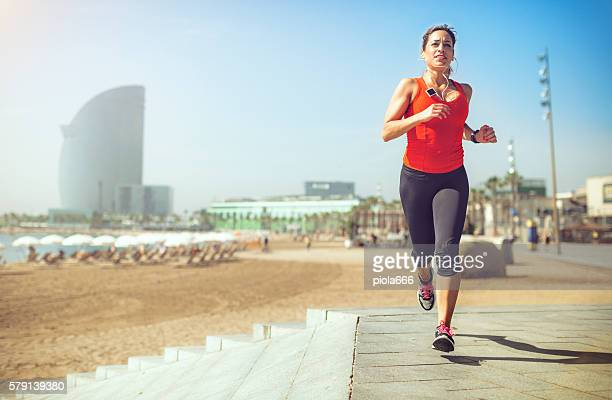 Sporty woman running and training by the beach