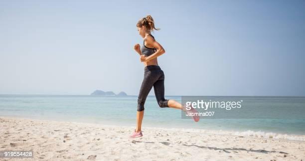 sportliche frau am strand - blond frauen strand stock-fotos und bilder