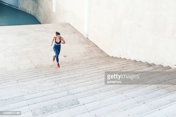 sporty woman running up steps in urban setting - forward athlete stock pictures, royalty-free photos & images