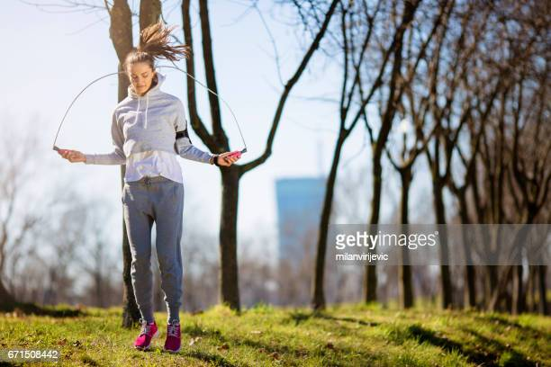 sporty woman skipping in a park - skipping along stock pictures, royalty-free photos & images