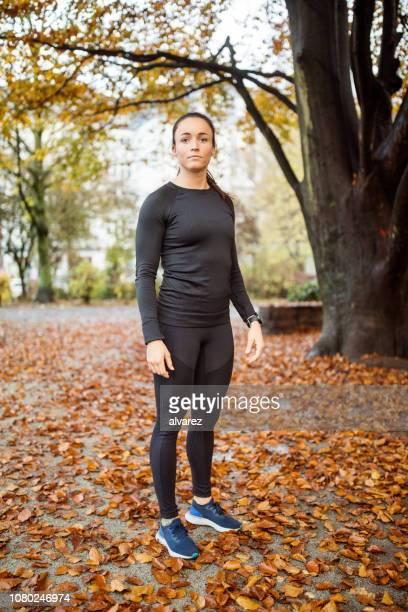 deportiva mujer de pie en el parque. - chándal fotografías e imágenes de stock