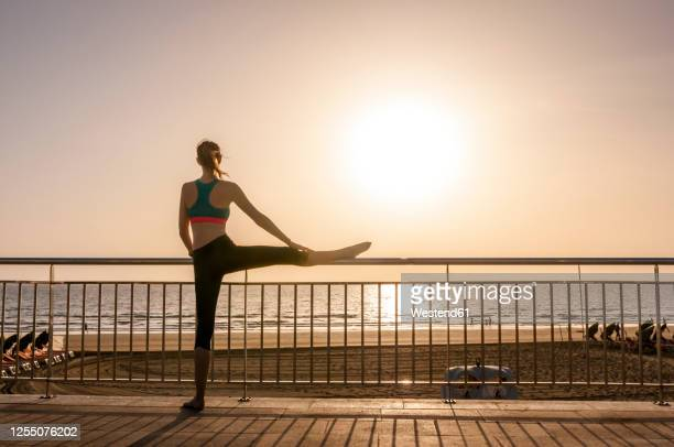 sporty woman stretching at the seafront at sunrise, gran canaria, spain - borde del agua fotografías e imágenes de stock