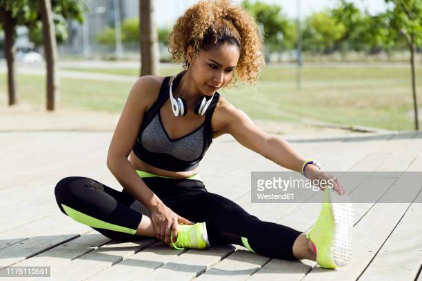 sporty woman stretching in the park - warming up stock pictures, royalty-free photos & images