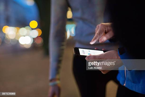 sporty woman using mobile phone on street - checking sports stock pictures, royalty-free photos & images