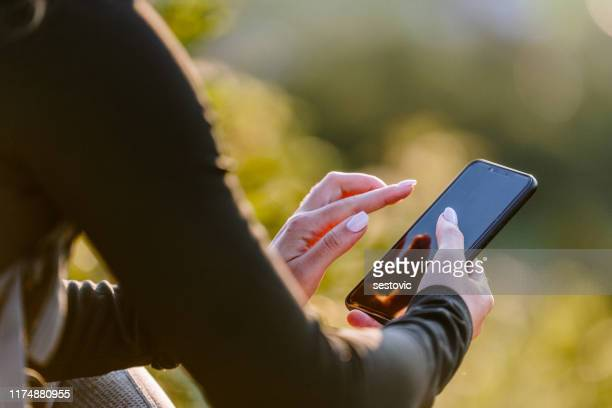 sporty woman using phone - phone message stock pictures, royalty-free photos & images