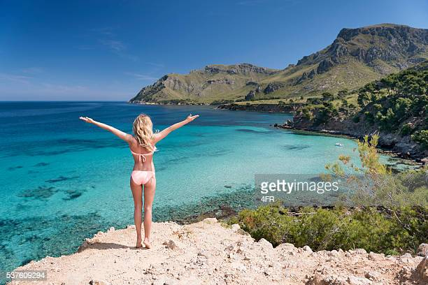 sporty woman with arms apart feeling nature, mallorca, spain - majorca stock pictures, royalty-free photos & images