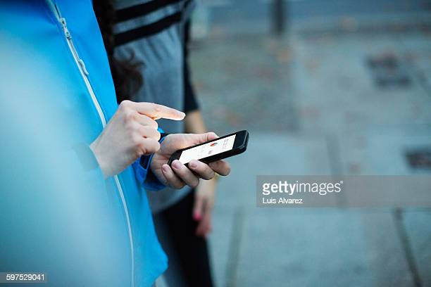Sporty woman with friend using smart phone in city
