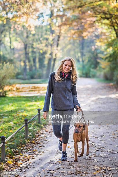 sporty woman with rhodesian ridgeback in park