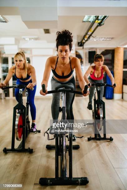 sporty women exercising on exercise bike at modern gym - peloton stock pictures, royalty-free photos & images