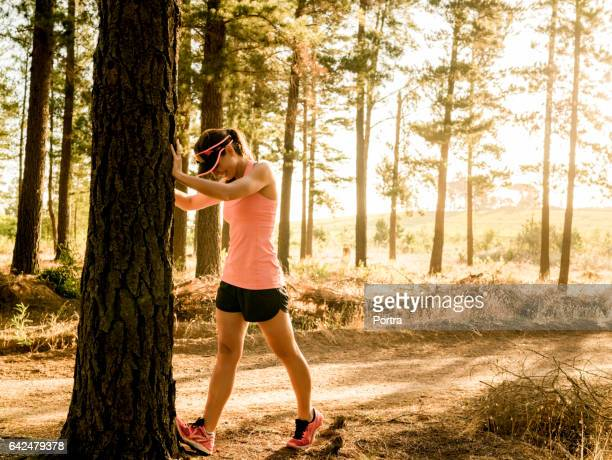 Sporty young female runner warming up at tree