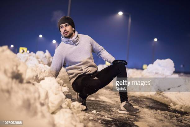 sporty young man getting up after a fall on a cold winter night. - down on one knee stock pictures, royalty-free photos & images