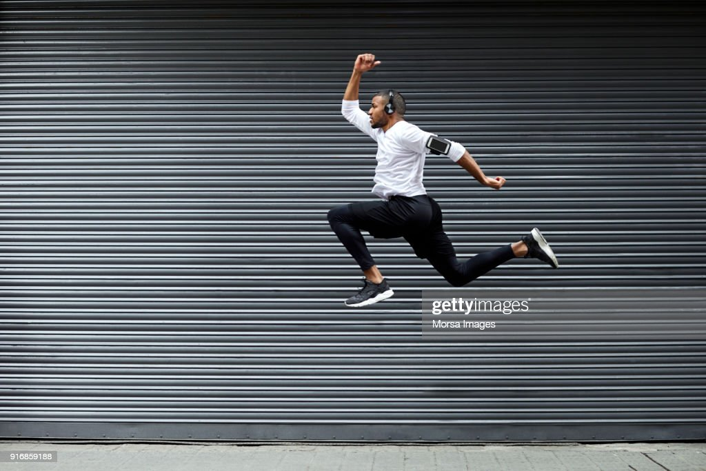 Sporty young man jumping against shutter : Stock Photo