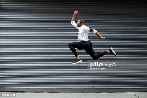 sporty young man jumping against shutter - vita cittadina foto e immagini stock