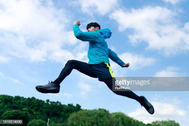 Sporty young man jumping and running outdoors