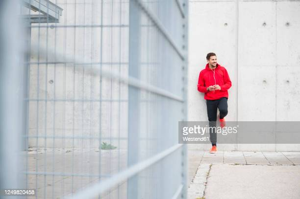 sporty young man listening to music at a concrete wall - sportsperson stock-fotos und bilder