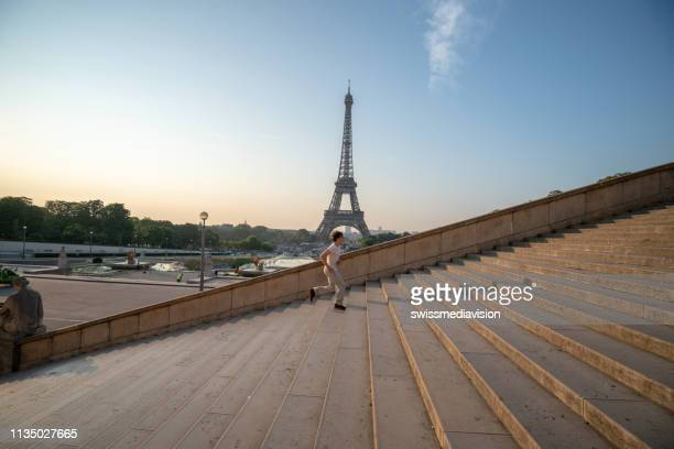 sporty young man running up the stairs at the eiffel tower in paris - tower stock pictures, royalty-free photos & images