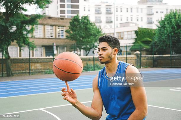 Sporty Young Man Spinning Basketball On Finger