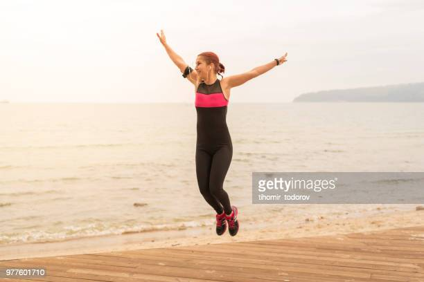 Sporty young woman being happy near the sea