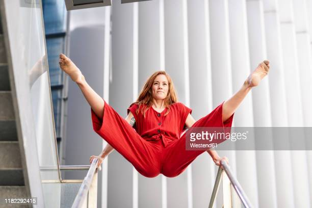 sporty young woman doing acrobatics on a railing - benen gespreid stockfoto's en -beelden