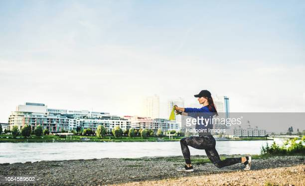 A sporty young woman doing exercise with elastic band outdoors on a riverbank in the city. Copy space.