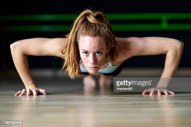 sporty young woman doing push-ups in exercise room - home workout stock pictures, royalty-free photos & images