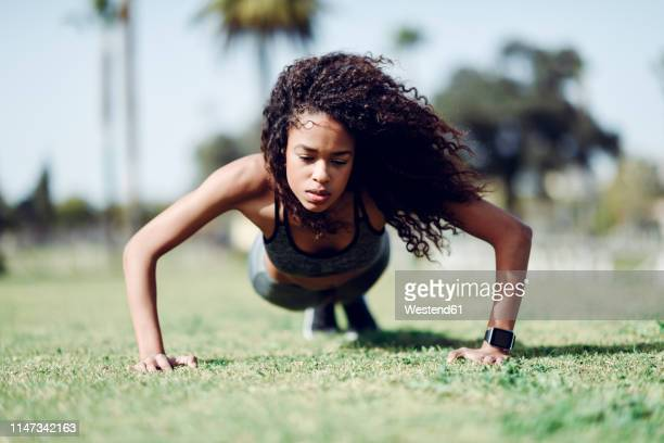 sporty young woman doing push-ups on lawn - extra long stock pictures, royalty-free photos & images