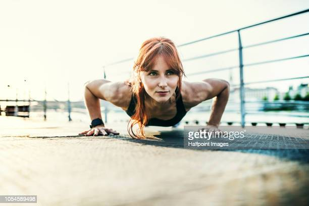 A sporty young woman doing push-ups on the bridge outdoors in the city.