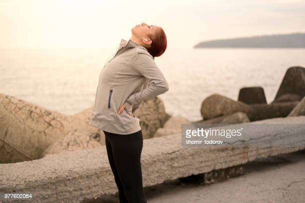 sporty young woman having back pains during workout - backache stock pictures, royalty-free photos & images