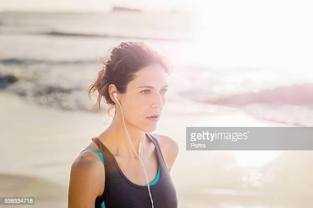 スポーティな若いを見ている女性距離にあるビーチ