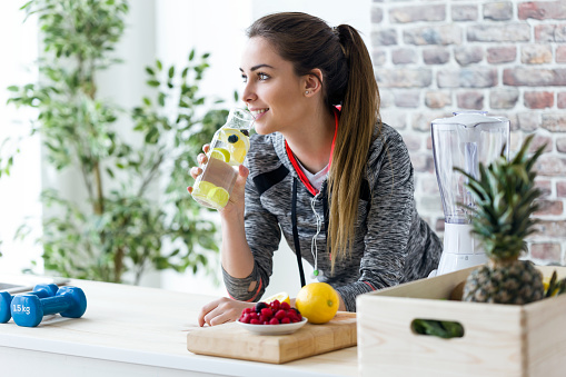 Sporty young woman looking sideways while drinking lemon juice in the kitchen at home. 952025532